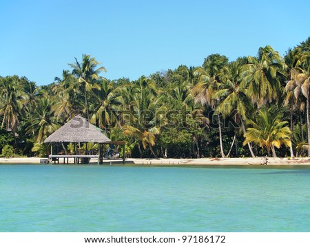 Tropical beach with thatch hut overwater, Caribbean sea, Panama - stock photo