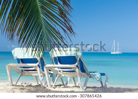 Tropical beach with two chairs. - stock photo