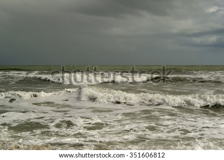 Tropical beach with waves breaking and stormy dark sky - cape Canaveral - stock photo