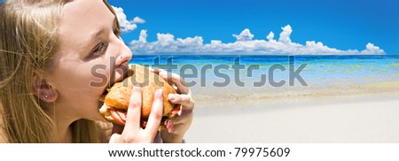 Tropical beach with young woman eating a bacon burger