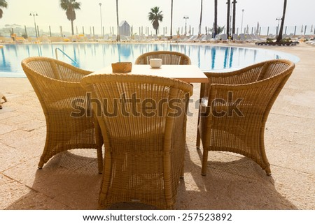 tropical cafe in front of pool by seaside - stock photo