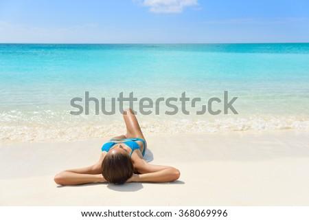Tropical Caribbean beach vacation - suntan relaxation woman. Bikini girl lying down relaxing on white sand exotic destination sleeping and sunbathing during summer holidays. - stock photo