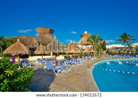 Tropical, caribbean swimming pool with some grass beach umbrellas in the luxury mexican resort. Bahia Principe, Riviera Maya. - stock photo