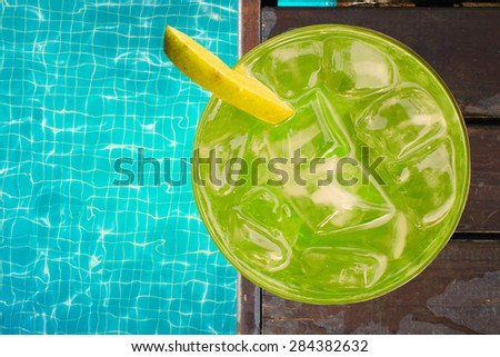 Tropical cocktail near swimming pool - stock photo