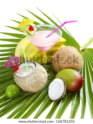 Tropical cocktail with coconut milk served on palm leaf. - stock photo