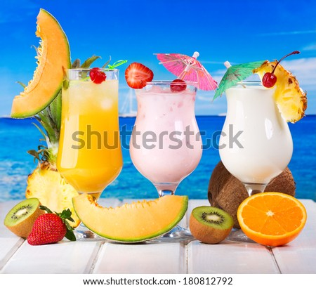 tropical cocktails with fresh fruits on a beach - stock photo