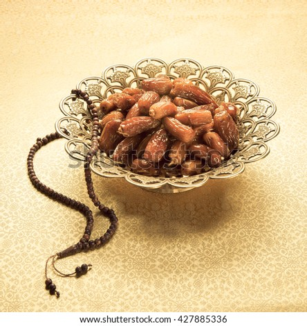 Tropical date fruits in an ornamental golden bowl with Islamic prayer beads. Ramadan  - stock photo