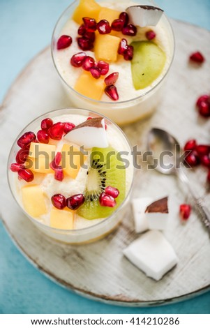 Tropical dessert with kiwi and pomegranate seeds in glasses