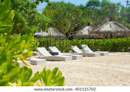 tropical empty beach view with sun loungers and waves - stock photo