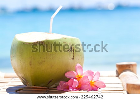 Tropical fresh coconut cocktail decorated plumeria on white beach - stock photo