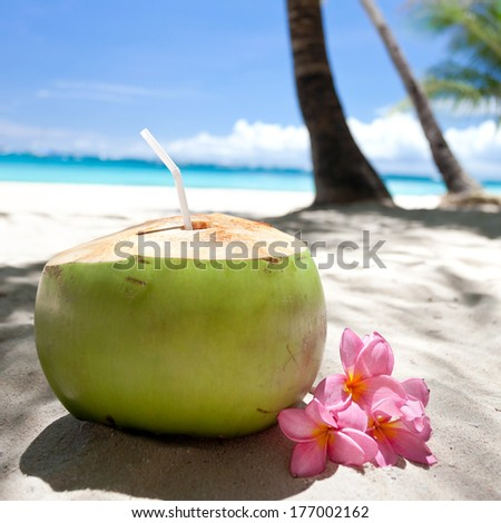 Tropical fresh coconut cocktail decorated plumeria on white beach, focus on straw - stock photo