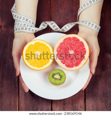 Tropical fruit on a white plate. Women's hands holding a plate of fruit. The concept of diet and weight loss. Hands of woman, wrapped in a measuring tape. - stock photo