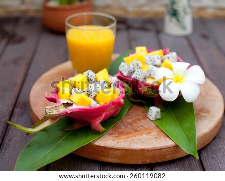 Tropical fruit salad in pitahaya, dragon fruit bowls with a glass of mango juice and flower on a wooden background - stock photo