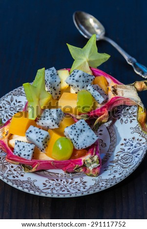 TropicaL fruit salad served in half a dragon fruit on black wooden background, selective focus