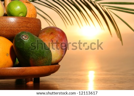 Tropical fruits arrangement infront of the sunset at the beach