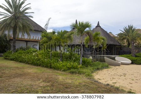 Tropical garden with bungalows on Mauritius island - stock photo
