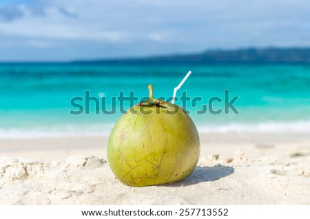 Tropical green coconut cocktail with drinking straw on a sand against background of turquoise sea lagoon at exotic white sandy beach on paradise Boracay island, Philippines. - stock photo
