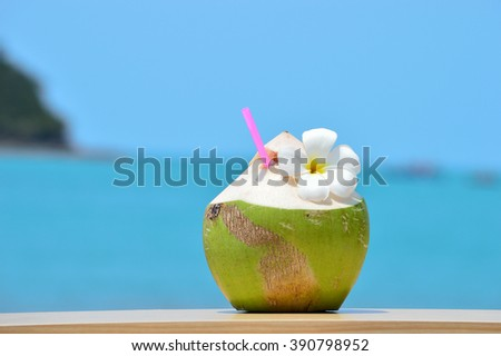 Tropical green coconut with drinking straw on wood table against background of turquoise sea - stock photo