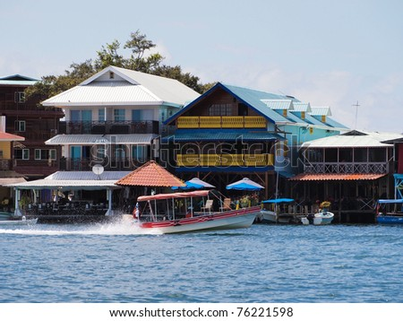 Tropical hotel restaurant over water with boat, Bocas town, Caribbean sea, Bocas del Toro, Panama