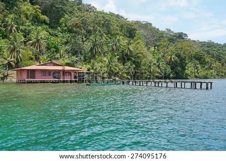 Tropical house with dock over the sea and luxuriant tropical vegetation on the land, Caribbean coast of Panama, Bocas del Toro - stock photo