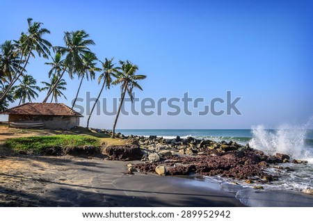 Tropical Indian village with coconut palm trees near the road and blue ocean in Varkala, Kerala, India - stock photo
