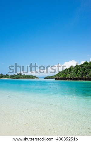 Tropical island beach lagoon paradise with clear blue sky and clear turquoise water - stock photo