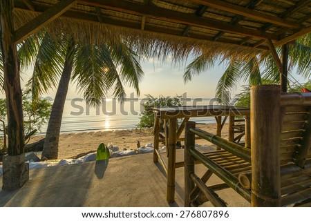 Tropical island hut on beach at sunset - stock photo