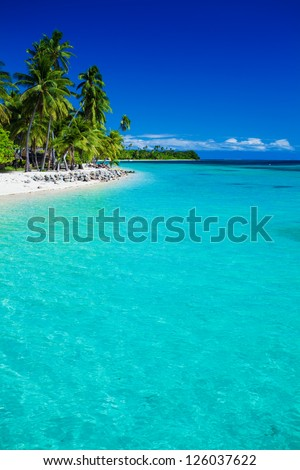 Tropical island in Fiji with sandy beach and pristine water - stock photo