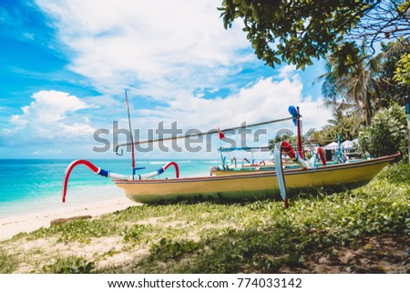 Tropical island in Indonesia, blue ocean and traditional boats on a sandy beach