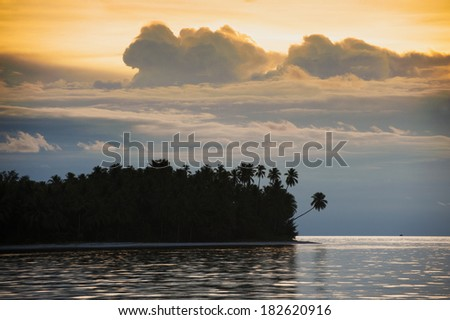 "Tropical Island Sunset. An uninhabited island seen in the remote and exotic Maluku area of Indonesia with palm trees and white sandy beaches. Also known as the ""Spice Islands"" west of  Sulawesi."