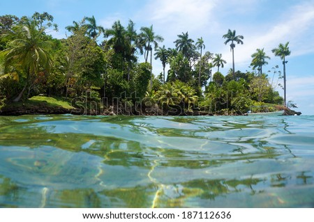 Tropical island with lush vegetation and a boat on mooring buoy, viewed from the water surface of the Caribbean sea, Panama, Bocas del Toro - stock photo