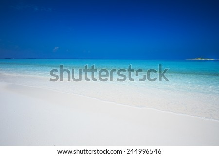 Tropical island with sandy beach with turquise clear water - stock photo