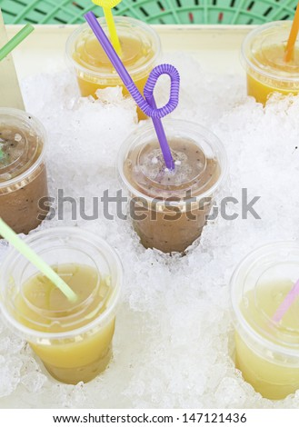 Tropical juices with straws and ice in drinks station, celebration