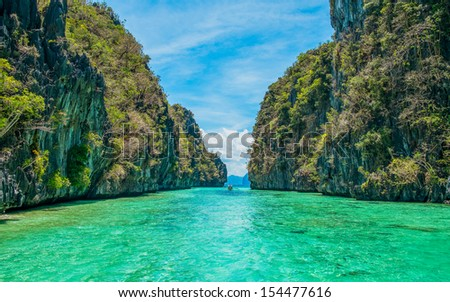 Tropical landscape - cristal clear water, rock islands, lonely boat - stock photo
