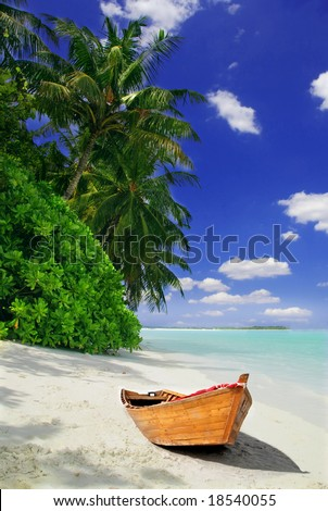 Tropical Maldivian beach with palms and wooden fishing ship - stock photo