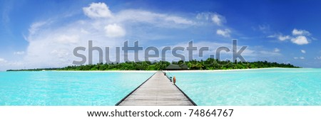 Tropical Maldivian paradise - a jetty leading to a beautiful tropical atoll hiden in the azure Indian ocean. Wide panoramic photograph. - stock photo