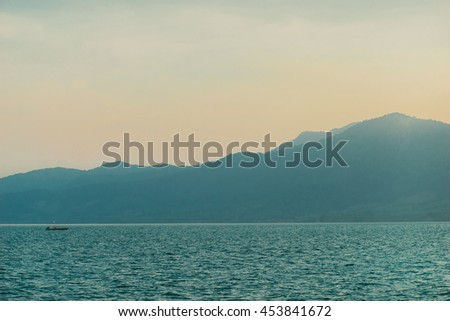 Tropical mountains covered in the mist near sea. Sunset. Travel inspiration. Postcard concept. Vacation wallpaper. Vintage effect.  - stock photo