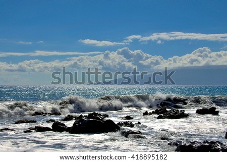 Tropical ocean beach waves breaking onto lava rocks located in beautiful travel destination Maui, Hawaii - stock photo