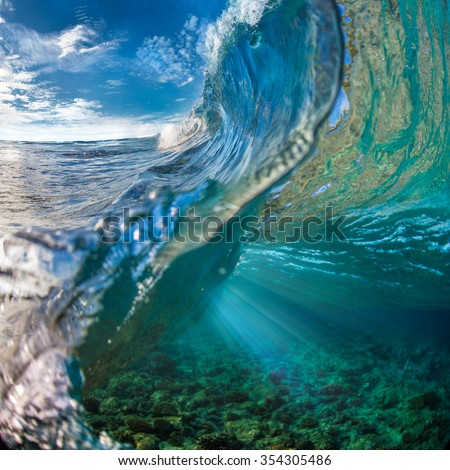 Tropical ocean with shorebreak. Surfing wave splashing on coral reef. Maldivian paradise with clouds on blue sky in daylight. View point from inside the wave - stock photo