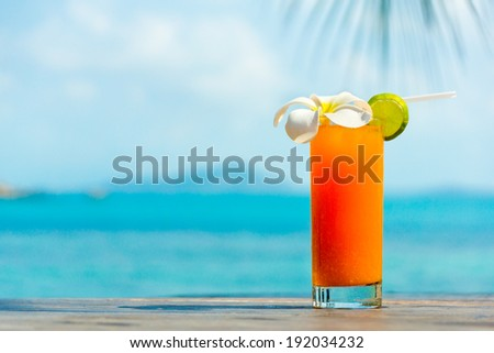 Tropical orange cocktail with Plumeria or Frangipani flower on the sea background - stock photo