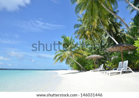 Tropical paradise beach and beach chairs -- Vacation concept - stock photo
