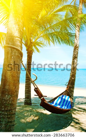 Tropical Paradise - Hammock between palm trees - stock photo
