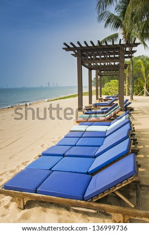 Tropical Paradise of sun beds on white sand beach. - stock photo