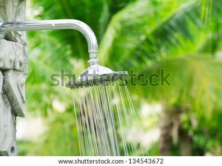 Tropical refreshing shower under palm trees - stock photo