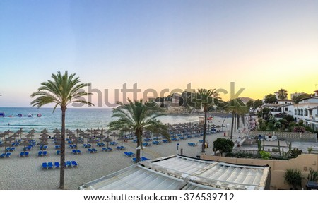 Tropical resort beachfront, Mallorca, Spain with rows of recliner chairs and palm trees against a beautiful sunset backdrop