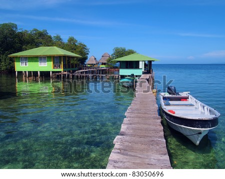 Tropical resort over the water with boat at dock and bungalows, Caribbean sea, Crawl Cay, Bocas del Toro, Panama - stock photo