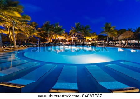 Tropical resort with swimming pool at night - stock photo