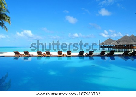 Tropical resorts swimming pool overlooking sea -- Maldives tropical island resorts - stock photo