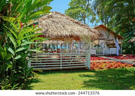 Tropical restaurant with thatched roof and colorful plants, Caribbean, Puerto Viejo de Talamanca, Costa Rica - stock photo