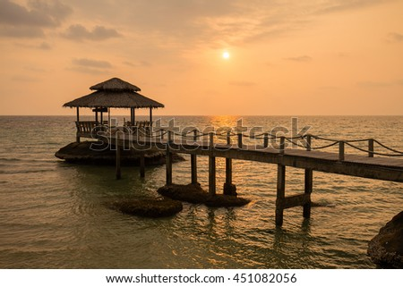 Tropical sand beach with pier near sea water on the sunset - stock photo